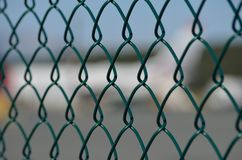 Airport fence closeup photo with blurred aircrafts. In the background Royalty Free Stock Photo