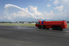 Airport Firetruck on the runway. Big red Airport Firetruck using a water cannon on the runway Stock Photos