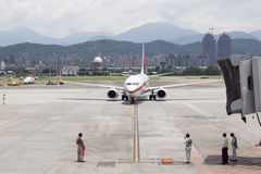 Airport ground service  await aircraft approaching with jet brid. Ge on tarmac  in Taipei SongShan Airport Stock Photos