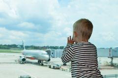 In airport hall child looks at the plane through window royalty free stock image