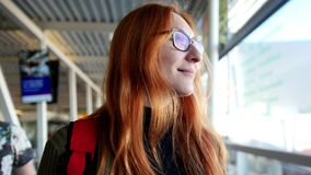 Airport - happy woman with red hair and glasses taking the escalator and looking to window stock video footage