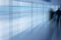 Airport interior blur. An interior view of passengers walking along a corridor of a busy international airport Royalty Free Stock Photo