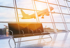 Airport interior with plane. Side view of airport terminal interior with seats, framed windows with city view, sunlight and an airplane flying by. 3D Rendering Royalty Free Stock Images