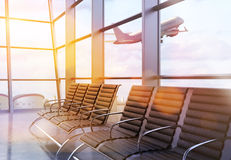 Airport interior with sunlight. Side view of airport interior with seats, framed windows with city view, sunlight and an airplane flying by. 3D Rendering Royalty Free Stock Images