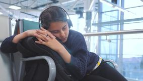 Airport lifestyle waiting hall room for a flight by plane. young happy teen girl in headphones listening to the music on. Airport lifestyle waiting hall room for stock video