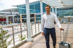 Airport lounge balcony and looking at airplane take off. Handsome Business man waiting for his flight. royalty free stock photography