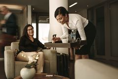Airport lounge waitress serving coffee to female passenger. Business lounge waitress serving coffee to female passenger at waiting area. Business women relaxing stock image