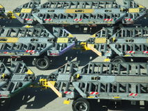 Airport luggage loading trolleys. Grey and yellow pattern made by luggage loaders on airport tarmac Stock Images
