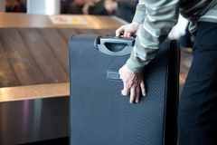 Airport luggage. Person with large suitcase in the airport luggage claim area stock photography