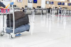 Airport luggage Trolley with suitcases, unidentified man woman walking in the airport, station, France Royalty Free Stock Photography