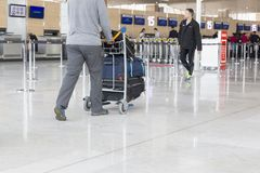 Airport luggage Trolley with suitcases, unidentified man woman walking in the airport, station, France Royalty Free Stock Photo
