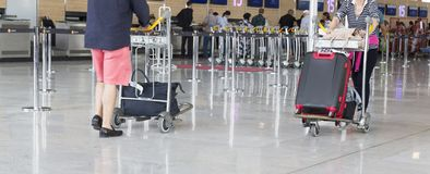 Airport luggage Trolley with suitcases, unidentified man woman walking in the airport, station, France Stock Photo