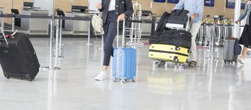 Airport luggage Trolley with suitcases, unidentified man woman walking in the airport, station, France. Royalty Free Stock Photography