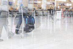 Airport luggage Trolley with suitcases, unidentified man woman walking in the airport, station, France. Blur motion, double exposu Royalty Free Stock Photography