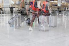 Airport luggage Trolley with suitcases, unidentified man woman walking in the airport, station, France. Blur motion, double exposu Royalty Free Stock Photos