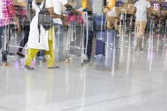 Airport luggage Trolley with suitcases, unidentified man woman walking in the airport, station, France. Blur motion, double exposu Stock Images