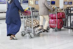 Airport luggage Trolley with suitcases, unidentified man woman walking in the airport, station, France Stock Photos