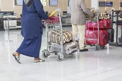 Airport luggage Trolley with suitcases, unidentified man woman walking in the airport, station, France Stock Image