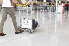 Airport luggage Trolley with suitcases, unidentified man woman walking in the airport, station, France Stock Images