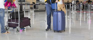 Airport luggage Trolley with suitcases, unidentified man woman walking in the airport, station, France Royalty Free Stock Photos