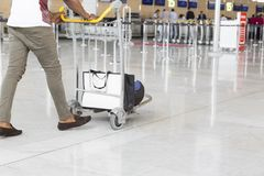 Airport luggage Trolley with suitcases, unidentified man woman walking in the airport, station, France. Royalty Free Stock Photo