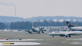 Airport movement in Munich Airport MUC. Air China and Lufthansa planes move in Munich Airport MUC. Winter weather conditions with snow on runways stock video