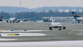 Airport movement in Munich Airport MUC. Plane movement in Munich Airport MUC. Winter weather conditions with snow on runways stock video