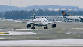 Airport movement in Munich Airport MUC. Plane movement in Munich Airport MUC. Winter weather conditions with snow on runways stock footage