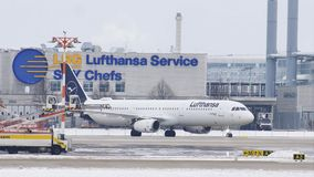 Airport movement in Munich Airport MUC. Plane movement in Munich Airport MUC. Winter weather conditions with snow on runways. Lufthansa Service SKY Chefs stock footage