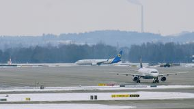 Airport movement in Munich Airport MUC. Planes move in Munich Airport MUC. Winter weather conditions with snow on runways stock video