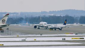 Airport movement in Munich Airport MUC. Planes move in Munich Airport MUC. Winter weather conditions with snow on runways stock video footage