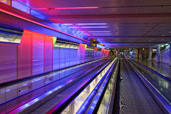 Airport moving walkway underground. Long moving walkways inside the building of the Munich airport, colorfully illuminated Royalty Free Stock Photography