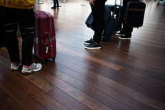 Airport, passengers awaiting boarding, legs and suitcases, close-up Stock Image