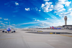 Airport. Planes departing at busy airport terminal with blue sunny background royalty free stock photography