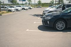 Airport Platov, Russia - 24.05.19: Parking with parked cars in sunny weather. Black business car parked on the street parking stock images