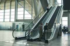 Airport Platov, Russia - 24.05.19: two adult men are climbing an escalator at the airport. Beautiful clean escalator at the airport royalty free stock photography