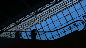 The airport or public place escalator scene: people silhouette on the staircase. Traveling concept: elevated male and female travellers group flying with transit stock video