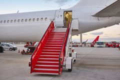 Airport runaway with airplane and stairway. Travel background. Sunset Stock Photography