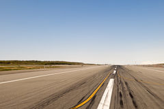 Airport runway. Low angle view of airport runway receding into distance under blue sky Royalty Free Stock Photography