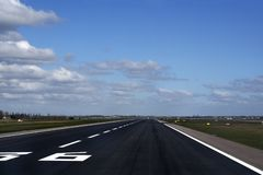 Airport runway. Asphalt runway on airport with plane taking of in the distance royalty free stock photos
