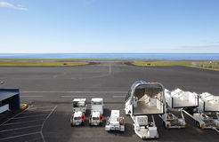 Airport runway close to the ocean with auxiliary vehicles Royalty Free Stock Photo