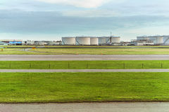 Airport runway in front of Fuel Storage Tanks and industrial storage site. Stock Image