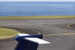 Airport runway near the ocean with aeroplane tale wing detail Stock Photography