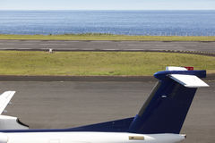 Airport runway near the ocean with aeroplane tale wing detail Stock Image