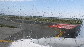 Airport runway view through moving plane window before the departure with rain drops stock video footage