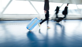 Airport rush. People with their suitcases walking along a corridor (motion blurred image; color toned image stock photos