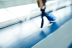 Airport rush. People with their suitcases walking along a corridor (motion blurred image; color toned image Royalty Free Stock Image
