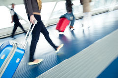 Airport rush. People with their suitcases walking along a corridor (motion blurred image; color toned image Royalty Free Stock Photos