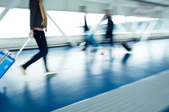 Airport rush. People with their suitcases walking along a corridor (motion blurred image; color toned image Stock Photography