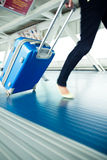 Airport rush. People with their suitcases walking along a corridor (motion blurred image; color toned image Stock Images